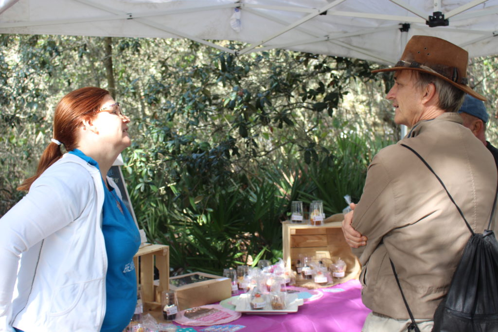 Two Garden Celebration attendees talk in front of a cupcake booth.